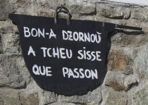 Napis na górskim domu w języku franko-prowansalskim (patois). Tłumaczenie: Dobrego dnia wszystkim, którzy tędy przechodzą.