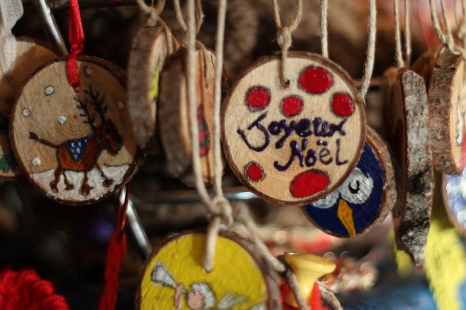 Ozdoby choinkowe z napisem Wesołych Świąt na jarmarku świątecznym w Bionaz.
