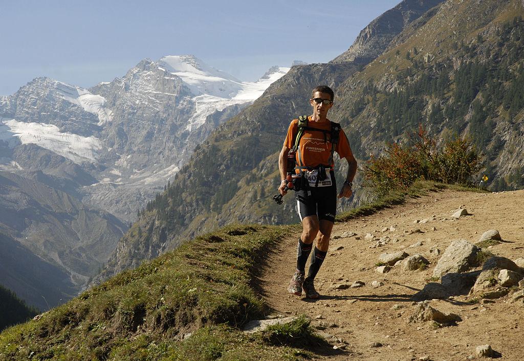 Jeden z uczestników Ultra Trail Tor des Geants na trasie, w tle Gran Paradiso. Źródło www.wikipedia.it