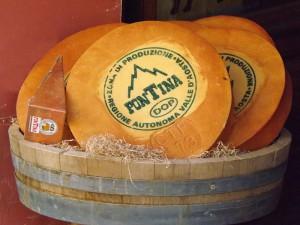 Okrągła forma sera Fontina z charakterystycznym logo.
