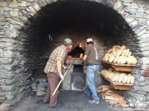Forno del vilaggio w Buthier i piekarze w akcji podczas wyciągania ciepłego chleba.