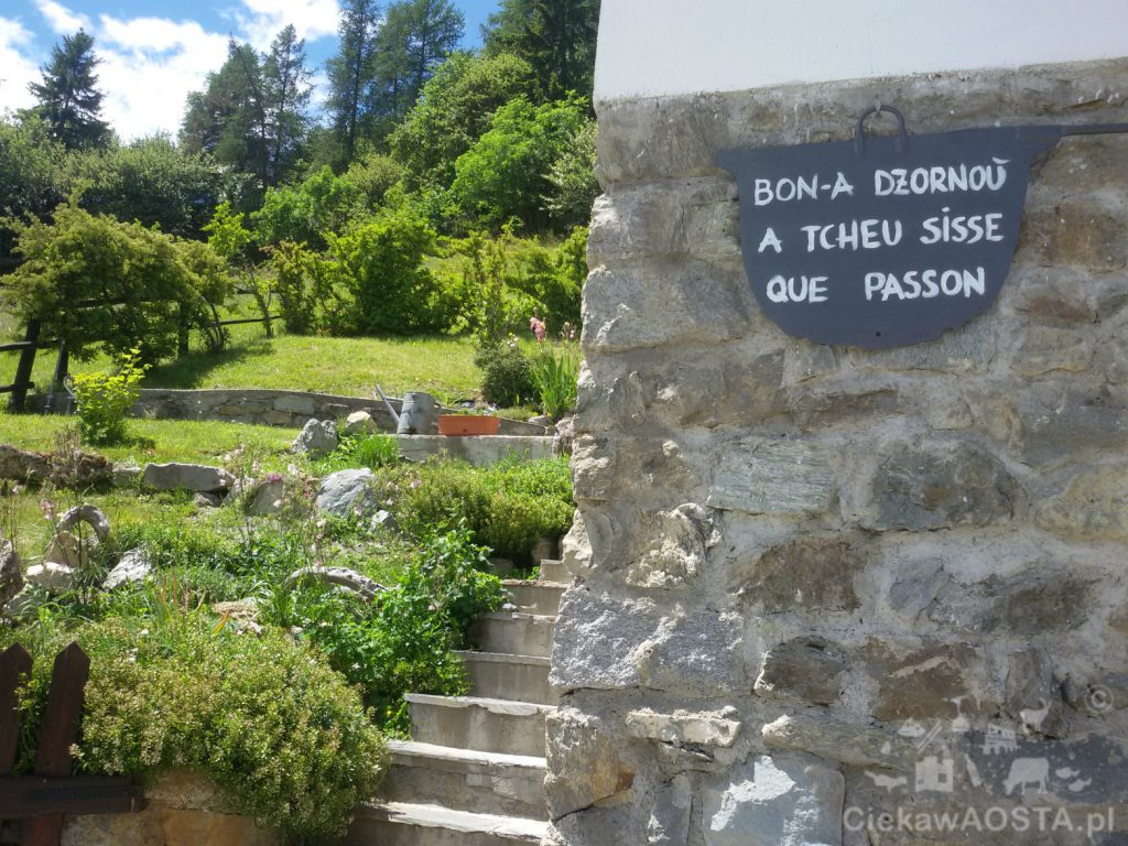 Dzień dobry dla tych którzy tędy przechodzą. Napis w języku franko - prowansalskim na domu w górach.
