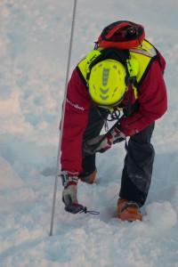 Ratownik alpejski przeszukuje po lawinie terytorium za pomocą sondy ARVA.