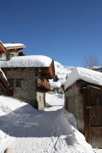 Dachy typowych alpejskich domów pokryte białym puchem w Chamois