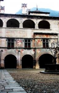 Zamek w Issogne. Na zdjęciu dziedzinieć z freskami na murach oraz słynna fontanna z drzewem granatowym. Źródło Wikimedia.it
