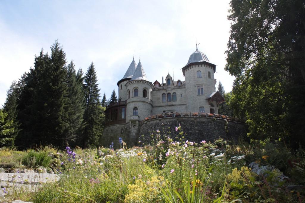 Zamek Savoia w Dolinie Lys, malowniczo położony, z widokiem na lodowiec Lyskamm masywu Monte Rosa. Na zdjęciu widać również alpejski ogród botaniczny.
