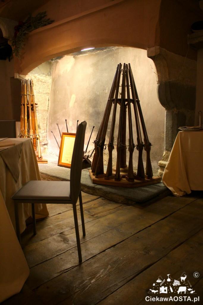 Kominek wewnątrz restauracji z ozdobami ze strzelb.